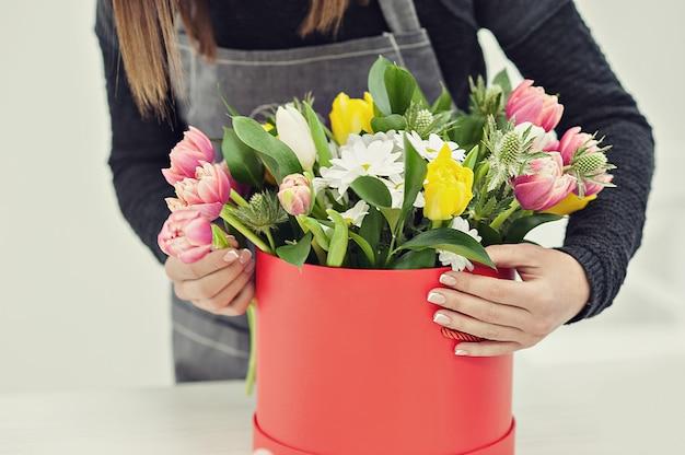 Zakończenie ręki kwiaciarnia z kwiatami. kwiaciarnia trzyma kwitnący bukiet różowi tulipany