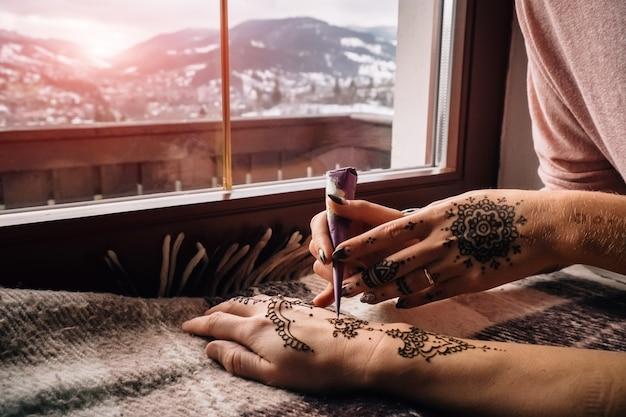 Zakończenie ręki mehndi ciała sztuka na zima krajobrazie