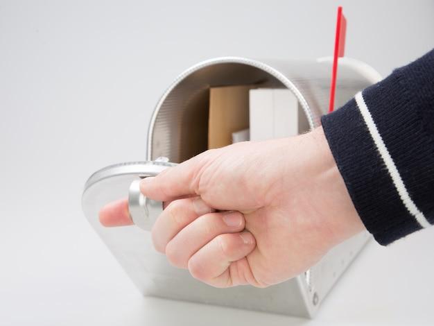 Zakończenie ręki mężczyzna patrzeje inside srebną skrzynkę pocztowa