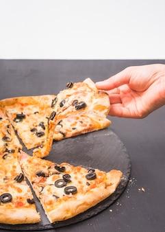 Zakończenie ręki mienia plasterek pizza na zmroku łupku