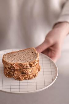 Zakończenie ręki mienia talerz z chlebem