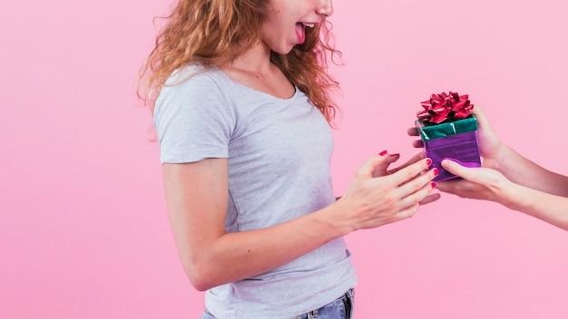 Zakończenie ręki mienie zawijał prezenta pudełko przeciw różowemu tłu