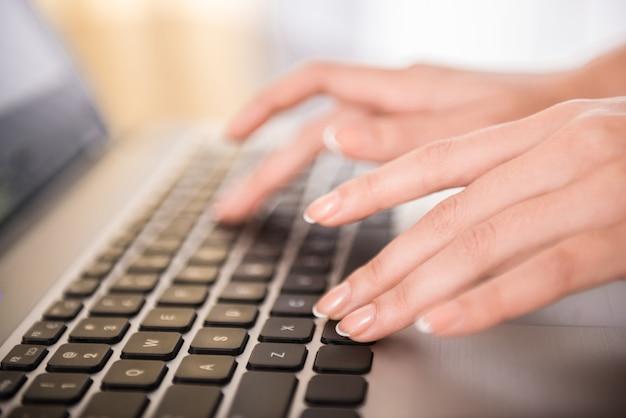 Zakończenie ręki pisać na maszynie na laptop klawiaturze w biurze.