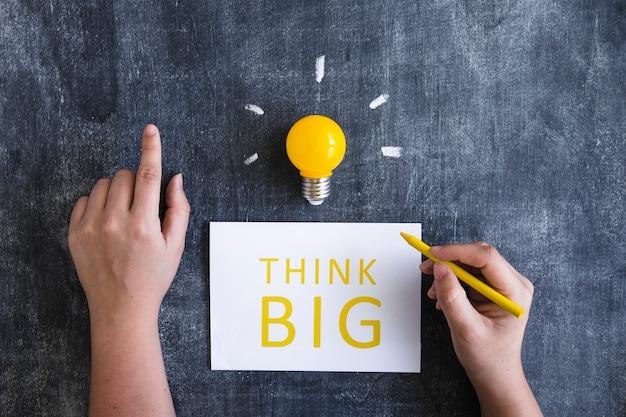 Zakończenie ręki writing tekst myśleć duży na białym papierze z żółtą żarówką na chalkboard