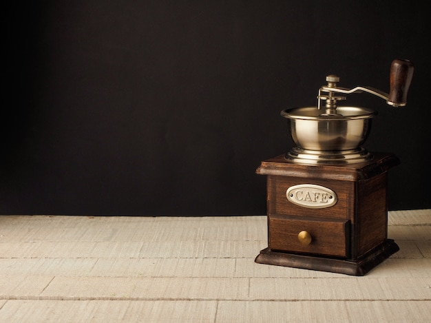 Zakończenie rocznika młynka do kawy młyn na ciemnym i lekkim drewnianym tle.