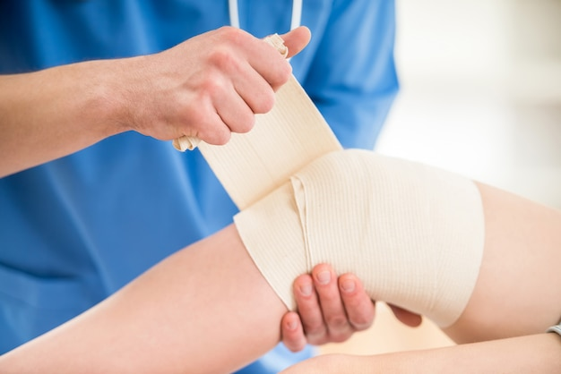 Zakończenie samiec lekarka bandażuje nogę z stetoskopem.