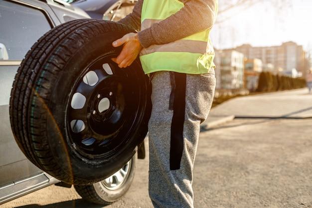 Zakończenie samochodowa opona. kierowca powinien wymienić stare koło na koło zapasowe.