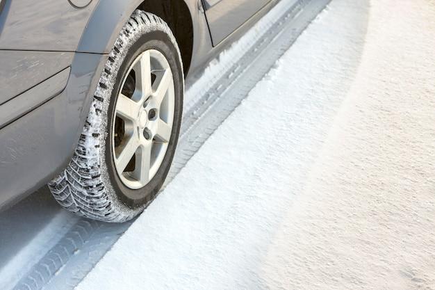 Zakończenie samochodowych kół gumowa opona w głębokim śniegu. koncepcja transportu i bezpieczeństwa.
