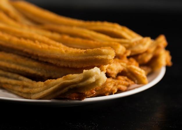Zakończenie smażący churros na talerzu