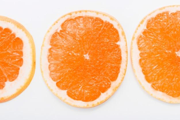 Zakończenie soczyści pomarańcz plasterki odizolowywający na białym tle