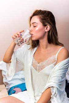 Zakończenie śpiąca młoda kobieta pije szkło woda w łóżku