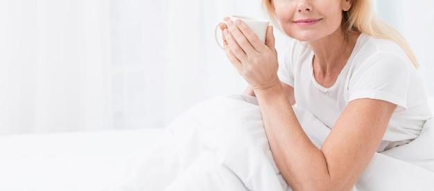 Zakończenie starsza kobieta cieszy się kawę w łóżku