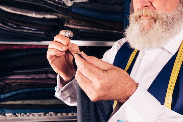 Zakończenie starszy męski projektant szy tkaninę z igłą