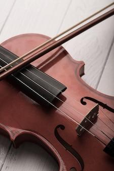 Zakończenie strzału skrzypcowa orkiestra instrumentalna z rocznika brzmieniem przetwarzającym nad białą drewnianą tło wybiórki ostrości płytką głębią pole