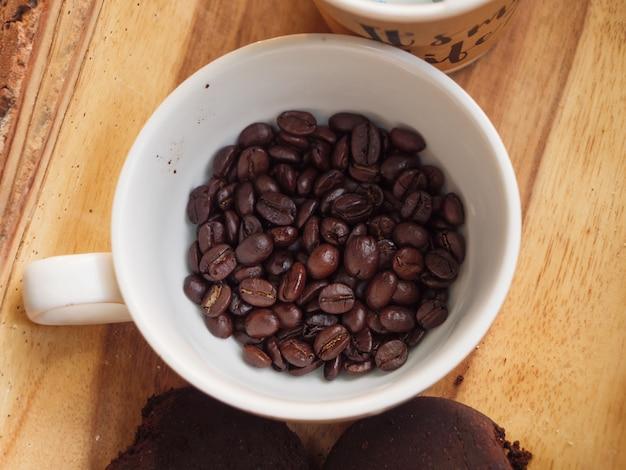 Zakończenie strzelał grupę piec kawową fasolę w białej filiżance przeciw drewnianemu stołowi wybiórki ostrości płytkiej głębii pole