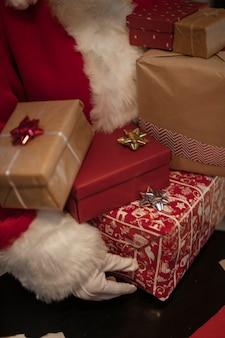 Zakończenie święty mikołaj trzyma prezentów pudełka