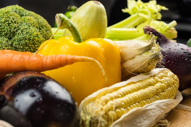 Zakończenie świezi organicznie warzywa na nieociosanym drewno stole. lokalnie uprawiana papryka, kukurydza i inne naturalne wegańskie jedzenie leżące na stole