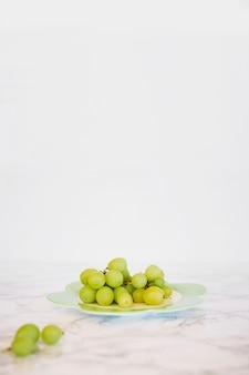 Zakończenie świezi zieleni winogrona na marmurze