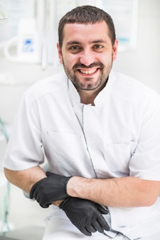 Zakończenie szczęśliwy męski dentysta patrzeje kamerę