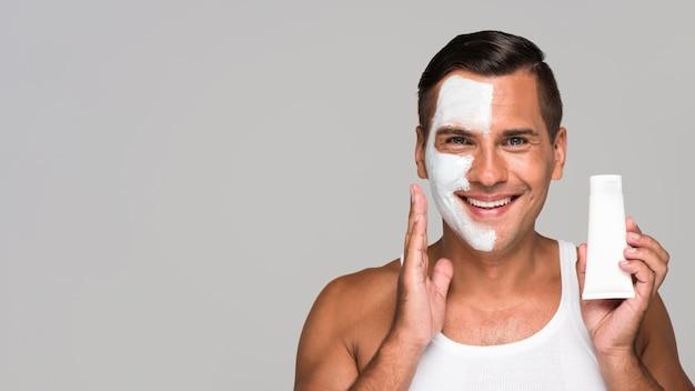 Zakończenie szczęśliwy mężczyzna trzyma produkt do twarzy