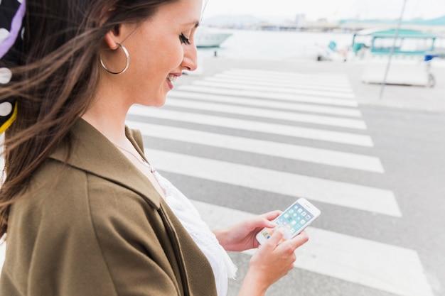 Zakończenie szczęśliwy młodej kobiety mienia telefon komórkowy