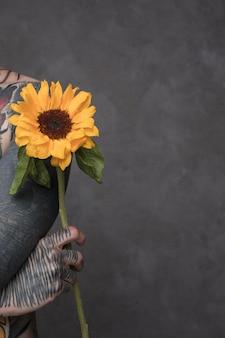 Zakończenie tatuażu młodego człowieka mienia słonecznik w ręce przeciw popielatemu tłu z copyspace