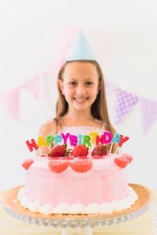 Zakończenie truskawkowy polewa tort z kolorowymi urodzinowymi świeczkami