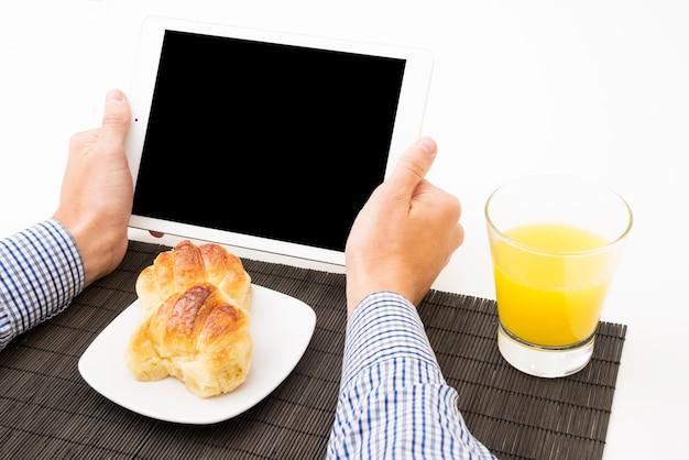 Zakończenie trzyma cyfrową pastylkę z pustym ekranem przy śniadaniowym mężczyzna ręka