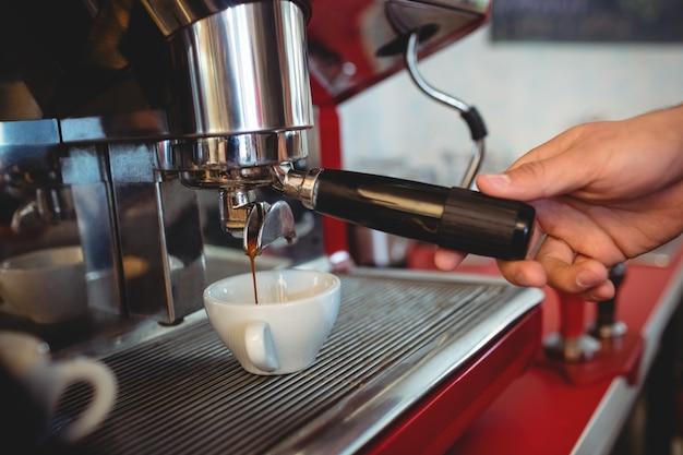 Zakończenie trzyma kawowego producenta rękojeść przy kawiarnią kelner