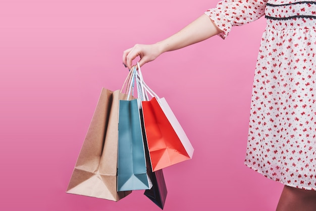 Zakończenie trzyma kolorowych torba na zakupy na menchiach żeńska ręka
