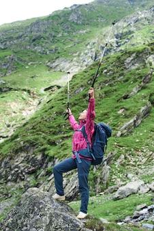 Zakończenie turystyczna dziewczyna stoi z rękami szeroko otwartymi na skale u podnóża góry. dziewczyna z plecakiem i kijami trekkingowymi