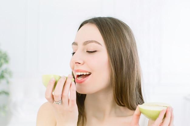 Zakończenie twarz piękna kobieta z czystą świeżą zdrową skórą, jedzący jabłka, pozuje i ono uśmiecha się. pojedynczo na białym tle