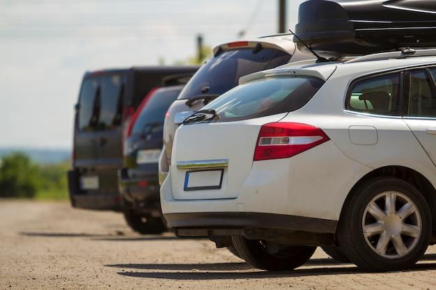 Zakończenie tylny widok biały drogi nowożytny samochód z czarnym bagażnikiem na dachu na rzędzie samochody i samochody dostawczy parkujący na asfalcie na jaskrawym słonecznym dniu. koncepcja transportu i parkowania.