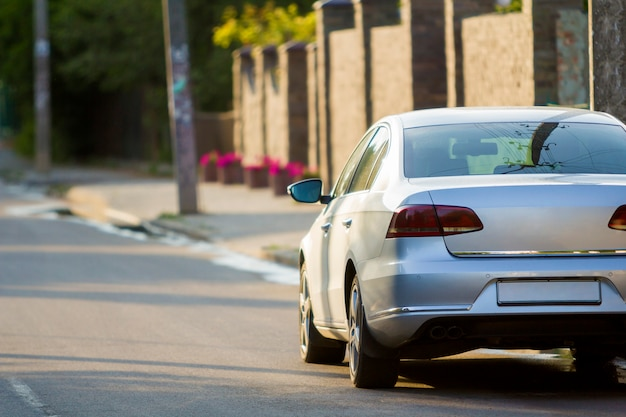 Zakończenie tylny widok nowy błyszczący drogi srebny samochodowy poruszający wzdłuż miasto ulicy na zamazanym drzewa, samochodów i budynków tle na pogodnym letnim dniu. wygodny transport i szybkość we współczesnym życiu.