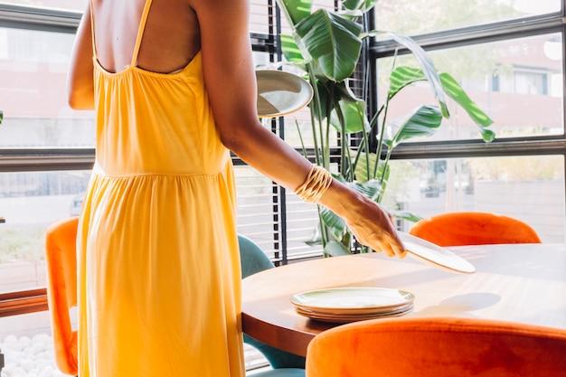 Zakończenie umieszcza dishware na round stole w restauraci kobieta