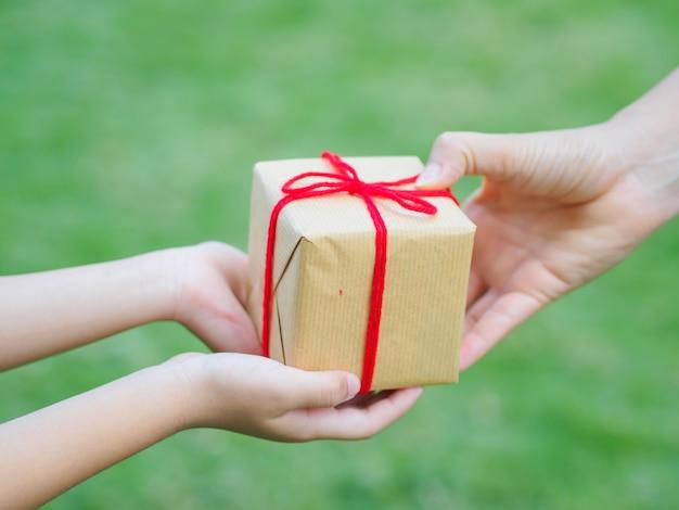 Zakończenie up dziecka i matki ręki z prezenta pudełkiem nad zielonym tłem.