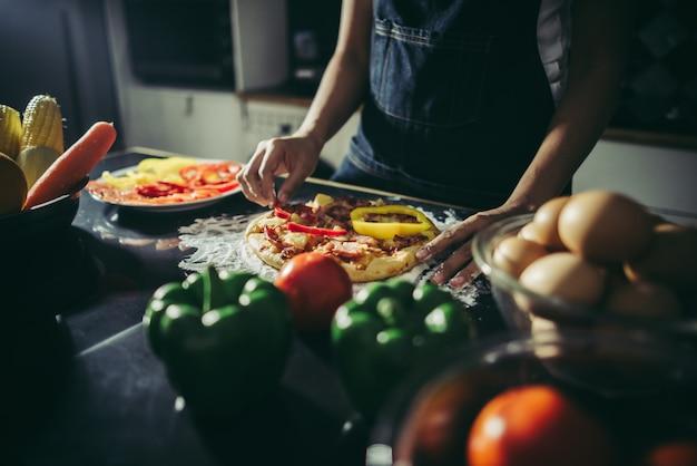 Zakończenie up kobiety ręka stawia polewa na domowej roboty pizzy.