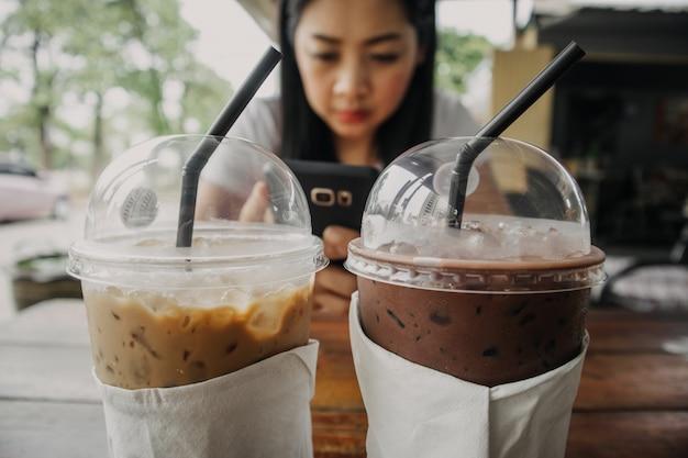 Zakończenie up lukrowa kawa i kakaowy napój w plastikowej filiżance na drewnianym stole.