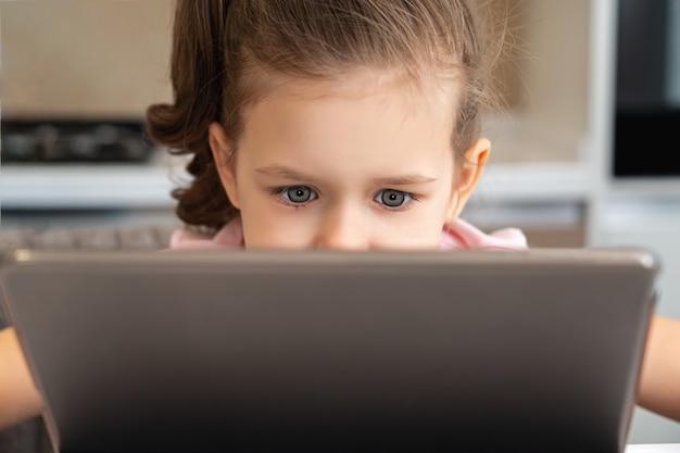 Zakończenie up mała dziewczynka patrzeje laptop lub pastylkę z kopii przestrzenią
