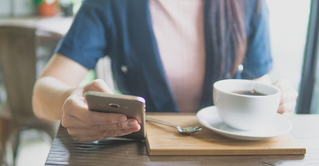 Zakończenie up młodych kobiet ręki trzyma mobilnego mądrze telefonu obsiadanie w kawiarni