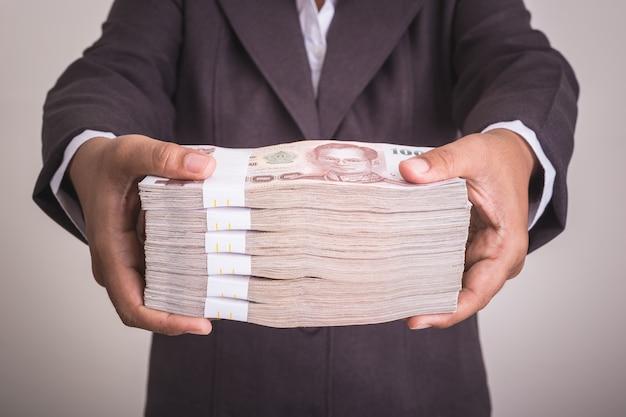 Zakończenie up ręka daje tajlandzkim banknotom. studio strzał na białym tle na szarym tle