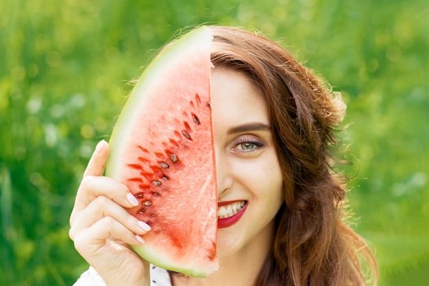 Zakończenie uśmiechnięta dziewczyna trzyma arbuza plasterek up zakrywa przyrodnią część twarz.