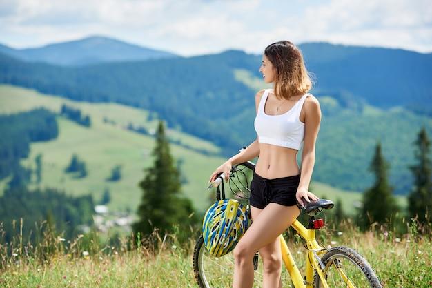 Zakończenie uśmiechnięta żeńska jeździec pozycja z żółtym rowerem górskim, cieszy się dolinnego widok przy letnim dniem. góry, lasy na niewyraźne. aktywność na świeżym powietrzu, koncepcja stylu życia