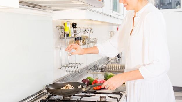 Zakończenie uśmiechniętej kobiety kulinarny jedzenie w kuchni