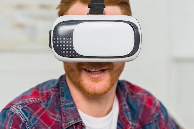 Zakończenie uśmiechnięty mężczyzna jest ubranym rzeczywistość wirtualna szkła