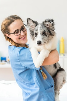 Zakończenie uśmiechnięty młody żeński weterynarz niesie psa w klinice