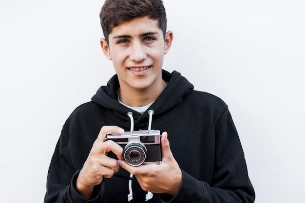 Zakończenie uśmiechnięty nastoletni chłopak trzyma retro kamerę