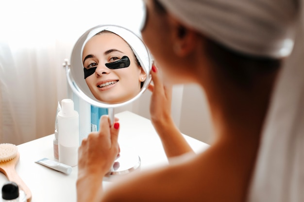 Zakończenie veautiful młodej dziewczyny spojrzenia w lustrze z łatami pod jej oczami. nad ramieniem widok dziewczyny w zabiegach kosmetycznych.