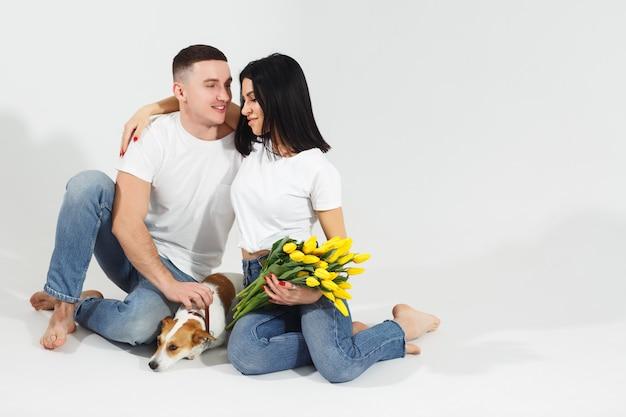 Zakończenie w górę portretów potomstw pary siedzi i ściska, trzymający żółtych kwiaty i psa w studiu na białym tle. para obejmująca z marzycielskim miłosnym wyrazem twarzy. kochana rodzina. świętujemy dzień kobiet.