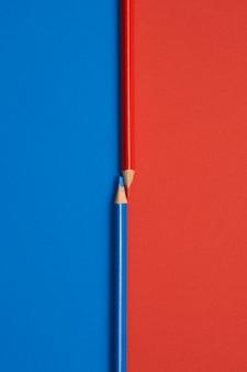 Zakończenie w obliczu czerwonych i błękitnych barwionych ołówków odizolowywających na stole błękitnym i czerwonym
